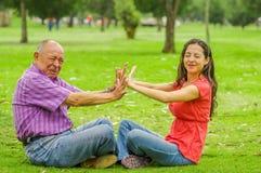 Utomhus- sikt av fadern och dottern som kasserar sig på det fria som sitter i gräset, i parkera arkivbild