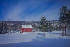 Utomhus- sikt av rött trätypisk housecovered med insnöat taket i GOL Royaltyfria Bilder