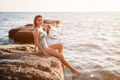 Utomhus- skott av att le den unga kvinnliga modellen i bikinianseende mot blå himmel Kvinna som har roligt ut på sommardag arkivbild