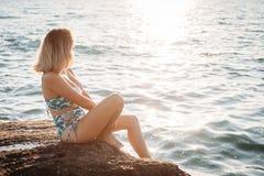 Utomhus- skott av att le den unga kvinnliga modellen i bikinianseende mot blå himmel Kvinna som har roligt ut på sommardag arkivbilder