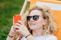 Utomhus- skott av den angenäma seende lockiga unga kvinnlign i solglasögon, telefon för modern apelsin för håll smart, sociala nä arkivfoto