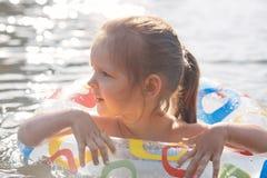 Utomhus- skott av den ganska haired roliga lilla flickan som spenderar fri tid i sjön som lär att simma med att simma cirkeln som arkivfoton