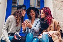 Utomhus- skott av tre unga kvinnor som ser smartphonen p? gatan roliga flickor som har samtal royaltyfri bild