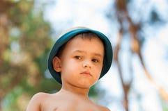 Utomhus- slut upp ståenden av pysen i en hatt Bakgrund en person, barn, 4-5 gamla år royaltyfria foton