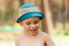 Utomhus- slut upp ståenden av pysen i en hatt Bakgrund en person, barn, 4-5 gamla år arkivbilder