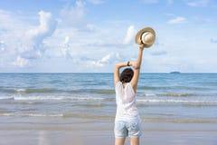 Utomhus- sommarstående av den unga asiatiska kvinnan som bär den stilfulla hatten och kläder som står på stranden som tycker om s royaltyfri fotografi