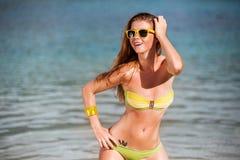 Utomhus- sommarstående av den unga nätta kvinnan i bikini nära havet på den tropiska stranden Arkivbilder