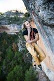 utomhus- sport Vagga klättraren dinglar i midair, som han kämpar för att klättra en utmanande klippa Arkivfoto