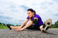 Utomhus- sportar - den unga kvinnan som gör kondition parkerar in royaltyfri fotografi