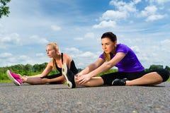 Utomhus- sportar - unga kvinnor som gör kondition parkerar in arkivbild