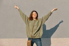 Utomhus- stående av att le den tonåriga flickan med armar som lyfts upp, grå solig väggbakgrund, sinnesrörelse av lycka och glädj arkivbilder