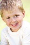 Utomhus- stående av att le den unga pojken Fotografering för Bildbyråer