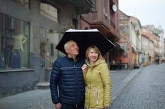 Utomhus st?ende av den ?ldre mannen och hans unga blondin-haired frun som omfamnar sig som st?r under deras paraply p? royaltyfri fotografi