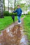 Utomhus- stående av den förtjusande pojken med paraplyet Arkivfoton