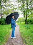 Utomhus- stående av den förtjusande pojken med paraplyet Royaltyfri Bild