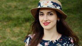Utomhus stående av den fantastiska flickan i sommarhatt med sinnliga röda kanter som ser kameran och le lager videofilmer