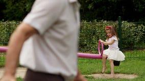 Utomhus stående av den gulliga flickan med den långa hår och kransen av röda blommor på lekplatsen under varm dag för sommar arkivfilmer