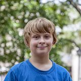 Utomhus- stående av den gulliga le unga pojken arkivbild