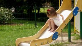 Utomhus stående av den gulliga lilla flickan som spelar på barnens glidbana på lekplatsen under sommar Sunny Day stock video