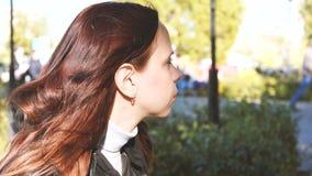 Utomhus stående av den härliga unga brunettflickan Le för kvinna som är lyckligt på solig sommar eller vårdag utanför på stadsbak arkivfilmer