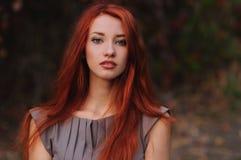 Utomhus stående av den härliga unga kvinnan med rött hår Royaltyfri Bild