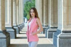 Utomhus- stående av den härliga unga kvinnan nära kolonn royaltyfri fotografi