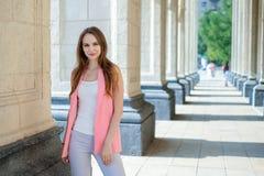 Utomhus- stående av den härliga unga kvinnan nära kolonn royaltyfria bilder