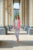 Utomhus- stående av den härliga unga kvinnan nära kolonn arkivbild