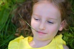 Utomhus stående av den lilla blonda flickan med blåa ögon som ligger på jordningen med stammen för grönt gräs i munnen Royaltyfria Bilder