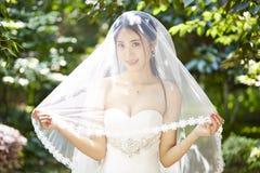 Utomhus- stående av den lyckliga asiatiska bruden arkivfoto