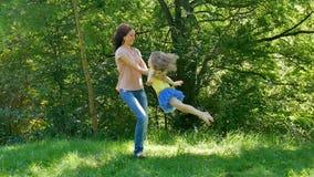 Utomhus stående av den lyckliga barnmodern i rosa skjorta och jeans som virvlar runt hennes gulliga lilla dotter i parkera under lager videofilmer