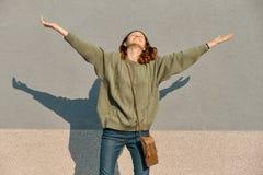Utomhus- stående av den lyckliga tonåriga flickan med händer upp och stängda ögon, grå solig väggbakgrund, sinnesrörelse av lycka fotografering för bildbyråer