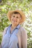 Utomhus- stående av den mogna kvinnan som bär Straw Hat arkivbilder