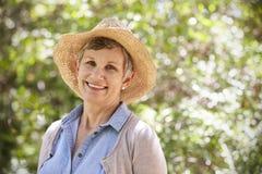Utomhus- stående av den mogna kvinnan som bär Straw Hat arkivfoton
