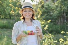 Utomhus- stående av den positiva mogna kvinnan i sugrörhatt Le kvinnlign med plattan av jordgubbemintkaramellcitronen, bakgrundsg royaltyfria bilder