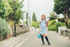 Utomhus- stående av den roliga lilla skolflickan Royaltyfri Foto