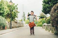 Utomhus- stående av den roliga lilla skolpojken Royaltyfri Foto