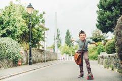 Utomhus- stående av den roliga lilla skolpojken Royaltyfria Bilder