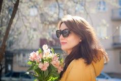Utomhus stående av den stilfulla attraktiva brunettkvinnan i solglasögon som utomhus går med den stora buketten av färgrikt royaltyfri bild