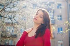 Utomhus stående av den stilfulla attraktiva brunettkvinnan som utomhus går under solig vårdag, medan solen skiner royaltyfri foto