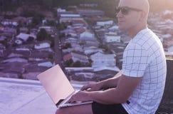 Utomhus stående av den stiliga unga mannen med bärbar datordatoren Royaltyfri Bild