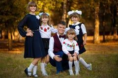 Utomhus- stående av den stora lyckliga familjen med en broder och fyra systrar royaltyfri foto