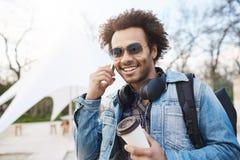 Utomhus- stående av den trendiga attraktiva mörkhyade mannen med bärande hörlurar för afro frisyr över hals som talar på royaltyfria foton