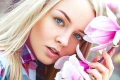 Utomhus stående av den unga blonda kvinnan för cutie med rosa blommor arkivfoton