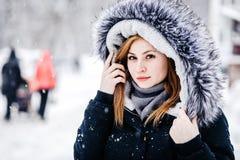 Utomhus- stående av den unga härliga flickan som bär i svart omslag med en huv Modell som poserar i gata Begrepp f?r vinterferier royaltyfria bilder