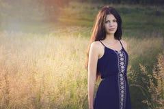 Utomhus- stående av den unga kvinnan på fältet Arkivfoton