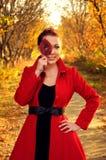 Utomhus- stående av den unga redheaded kvinnan i höstskog Royaltyfri Foto