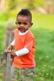 Utomhus- stående av en gullig ung liten svart pojke som spelar outsi Royaltyfri Bild