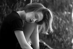 Utomhus- stående av en ledsen tonårs- flicka som ser fundersam om problemen, begreppet av sorgsenhet, ensamhet Arkivfoton