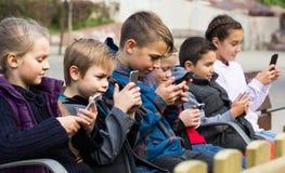 Utomhus- stående av flickor och pojkar som spelar med telefoner Royaltyfri Bild